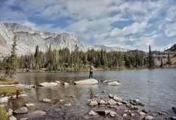 Fly Fisherman fishing remote backcountry high alpine lake. Fishing in Wyoming, Colorado, Montana and Idaho