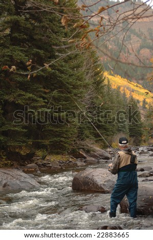 Fly Fisherman in a mountain stream with a fly rod