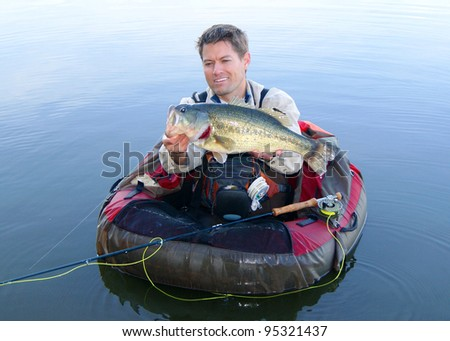 Fly fisherman in pontoon, float tube or belly boat, with large Largemouth Bass caught fishing with fly rod
