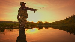Fly fisherman stands in the water and fishing on the river at sunset