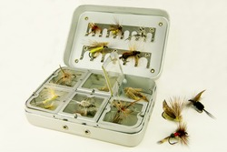Fly Fishing Box:  A well-used tackle box displays a variety of handmade lures for fly-fishing.
