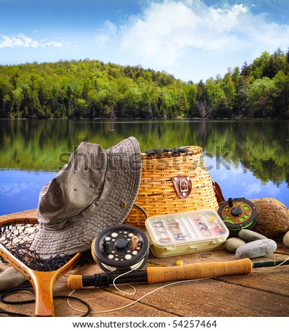 Fly fishing equipment on deck with beautiful view of a lake - stock photo
