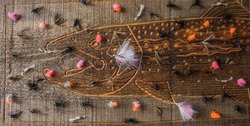 Fly Fishing Flies Laid Out on Old Retro Rustic Reclaimed Barn Plank Wood With a Salmon Trout Fish Pattern Carved Out