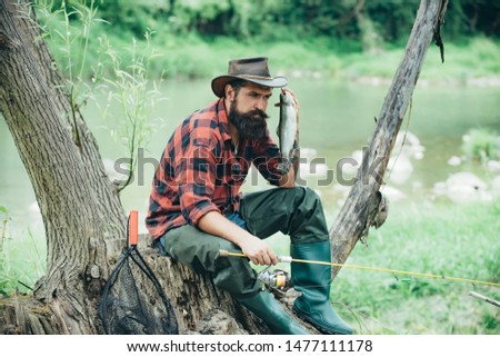 Fly fishing is most renowned as a method for catching trout and salmon. Fisher man fishing with spinning reel. Concepts of successful fishing #1477111178