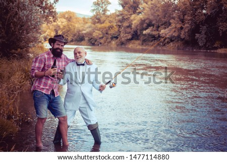Fly fishing is most renowned as a method for catching trout grayling and salmon. Fly fisherman using fly fishing rod in beautiful river. Man fisherman catches a fish #1477114880