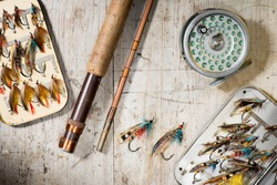 Fly fishing rod, reel and vintage salmon flies in boxes on a distressed white wooden background