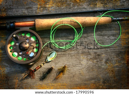 Fly fishing rod with  on wood background