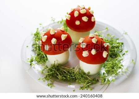 Fly mushroom formed from boiled egg, cover with the tomato mayonnaise. Funny food for children or party.