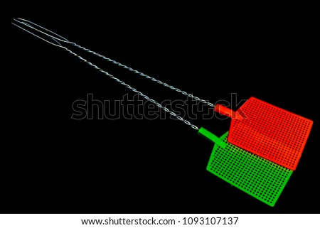 Fly swatters presented on plain black background. - Shutterstock ID 1093107137