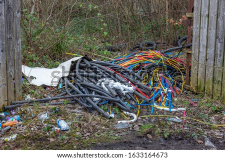 Fly-tipped illegally dumped plastic, metal, cables, tyres and rubbish in countryside. Compstall, Stockport, Cheshire, UK.