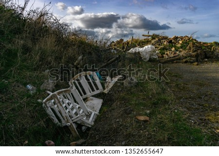 Fly Tipping In the Countryside with a White Broken Wooden Baby Cot Dumped in a Ditch with more Garden Waste around, with Blue Sky ad Clouds in the Sky.