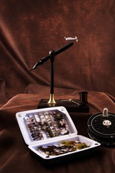 Fly tying vice, hand tied flies, and fishing reel.