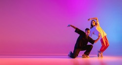 Flyer. Strange body movements. Two young people, guy and girl dancing contemporary dance over pink background in neon light. Modern dance aesthetics concept