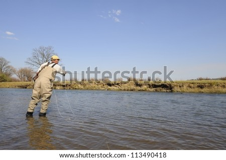 Flyfisherman. Fly-fishing for rainbow trout on the Umzimkulu River,Underberg,Southern Drakensberg,kwazulu Natal,South Africa - stock photo
