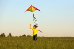 Flying a kite. the boy launches a kite. Summer day. Sunny.The boy in a yellow t-shirt with a kite. A boy of European appearance on the field. Sky. Vivid emotions