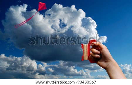 Flying a red kite in blue sky with clouds