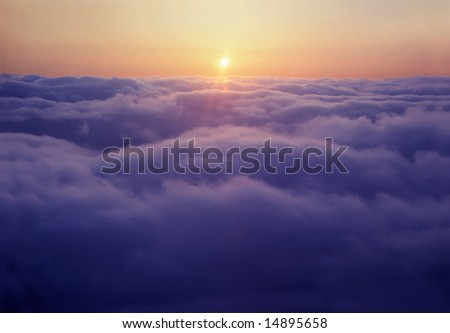 Flying above the clouds at sunset