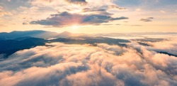 Flying above the clouds on drone. Panoramic morning view of Carpathian mountains with Homiak mountain on background. Fabulous sunrise on Ukraine, Europe. Beauty of nature concept background.