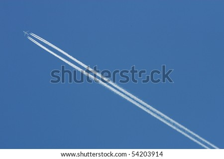Flying airoplane on the blue sky leaving white lines behind