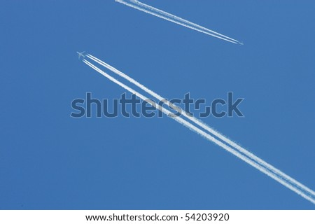 Flying airoplanes on the blue sky leaving white lines behind