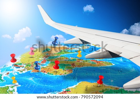 Flying around the world with aircraft wing overshadowing the earth map with pins marking future destinations  #790572094