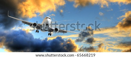 Flying away: panorama of airplane taking off in dramatic sunset sky with copy space.