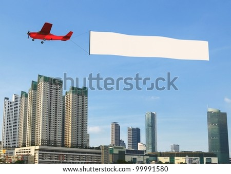 Flying banner pulled by airplane flying over a modern city building
