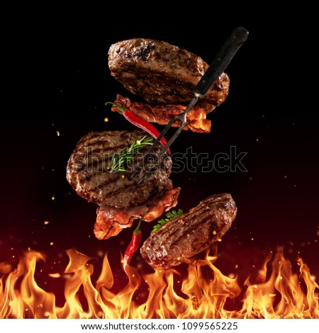 Flying beef minced hamburger pieces above grill flames, isolated on black background. Concept of flying food, very high resolution image #1099565225