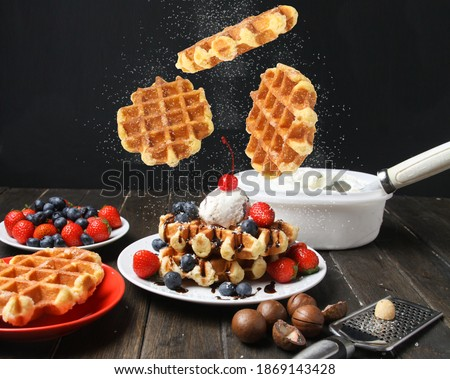 Flying Belgian Liege Waffles With Ice Cream, Berries And Topped Macadamia Nuts On Plate Powdered Sugar On Black Background. Side View. Foto stock ©