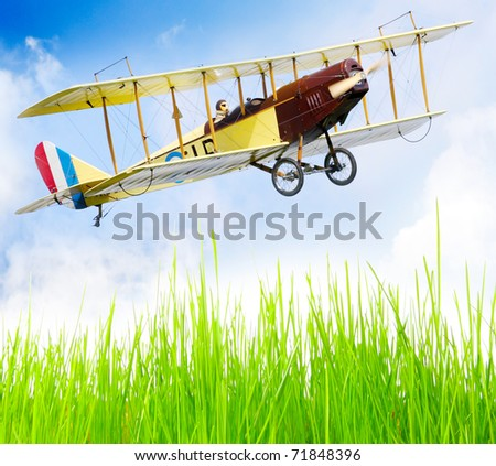 Flying biplane (homemade radio controlled scale-model 1:24 scale) over fresh spring grass on a airfield.