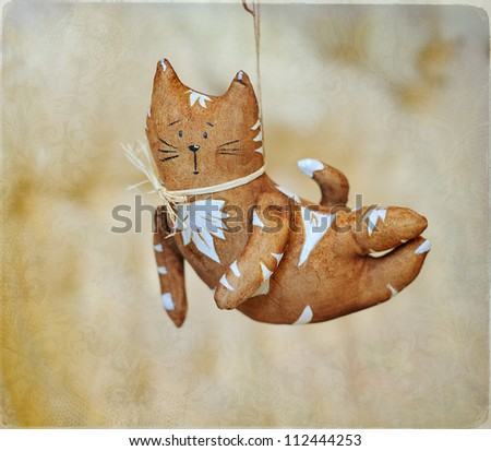 flying brown cat with white drawing and a bow