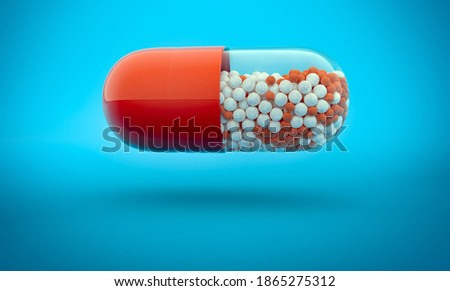 Flying capsule full of red and white granules on blue colored backdrop. 3d illustration of granular medication. Foto d'archivio ©