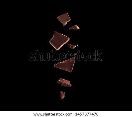 Flying chocolate pieces isolated on black backdrop. Falling fruit close up photo. Falling sweets against a black background close up photo.