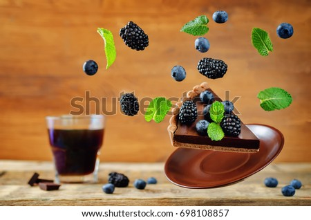 Flying chocolate tart with blackberries and blueberries. toning. selective focus #698108857