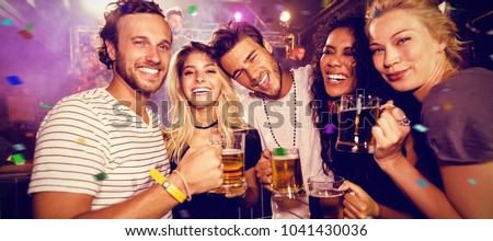 Flying colors against happy friends toasting beer mugs at club #1041430036