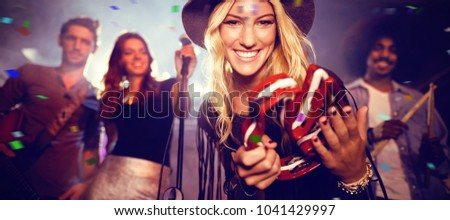 Flying colors against portrait of woman with musicians playing tambourine at nightclub #1041429997