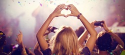 Flying colors against woman making heart shape while enjoying at nightclub