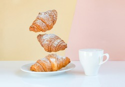 Flying croissants for breakfast and a cup of coffee on a beige background color sunrise. Levitating food, time to wake up call. Modern breakfast still life concept food.
