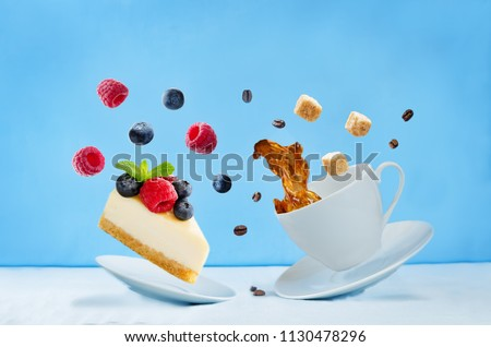 Flying cup of coffee with cheesecake on a blue background. toning. selective focus