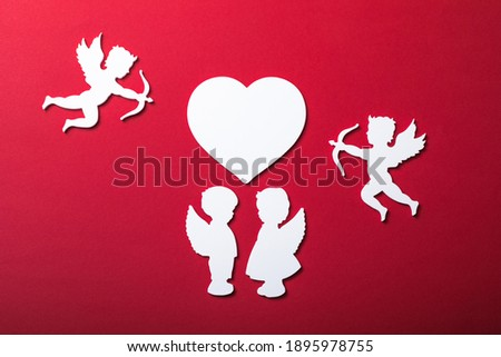 Photo of  Flying cupid silhouette, two white angel,  happy Valentine's Day banners, paper art style. Amour on red paper