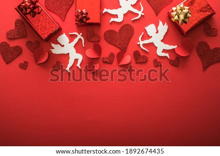 Photo of  Flying cupid silhouette with hearts, gifts, happy Valentine's Day banners, paper art style. Amour on red paper