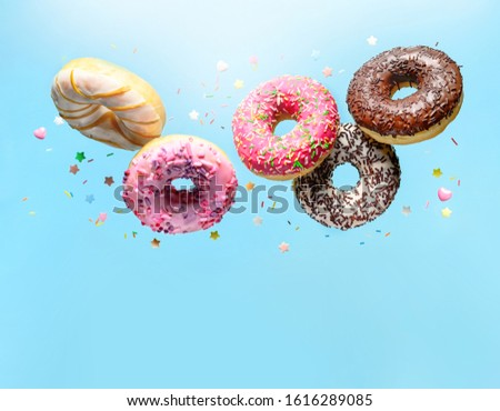 Flying donuts. Mix of multicolored doughnuts with sprinkle on blue background with copy space