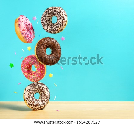 Flying donuts. Mix of multicolored sweet doughnuts with sprinkle on turqouise blue background falling on the table.