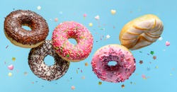 Flying donuts with sprinkle on blue background.