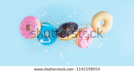 flying doughnuts - mix of multicolored sweet donuts with sprinkles on blue background