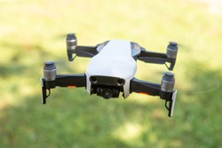 Flying drone with video camera with blurred green background