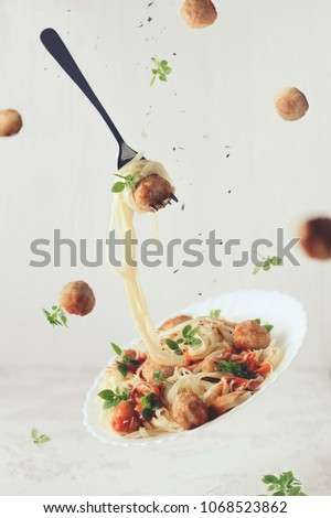 Flying food. Levitation of pasta fettuccine with meatballs, tomato sauce, basil on white concrete background #1068523862