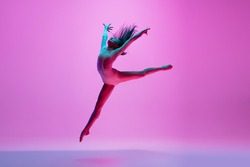 Flying, freedom. Young and graceful ballet dancer on pink studio background in neon light. Art, motion, action, flexibility, inspiration concept. Flexible caucasian ballet dancer, moves in glow.