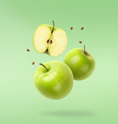 Flying fresh green apple with seeds on green background. Creative levitation food, summer fruits