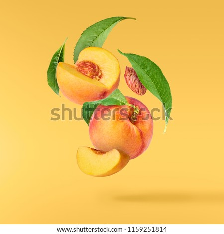 Flying fresh ripe peach with green leaves isolated on yellow background. Concept of food levitation, high resolution image